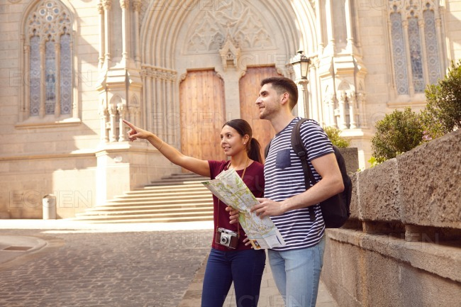 Young tourist couple on vacation pointing stock photo