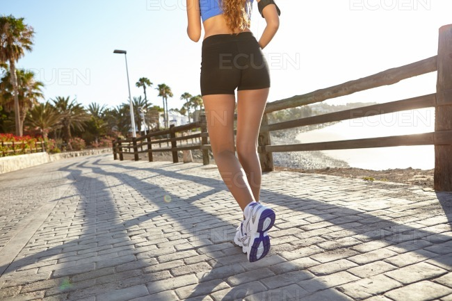 Young woman jogging outside in summertime stock photo