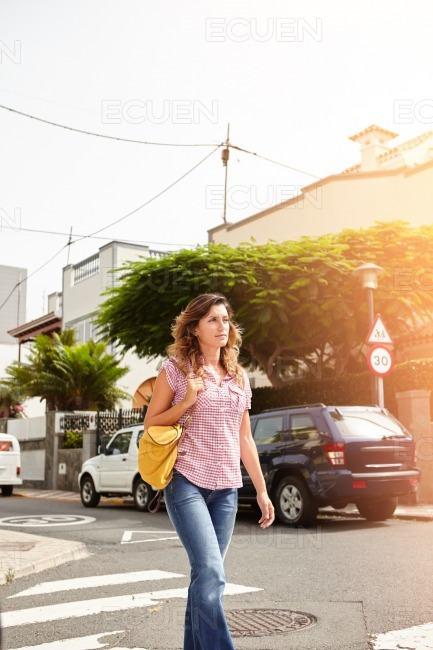 Young woman walking down a brightly lit street stock photo