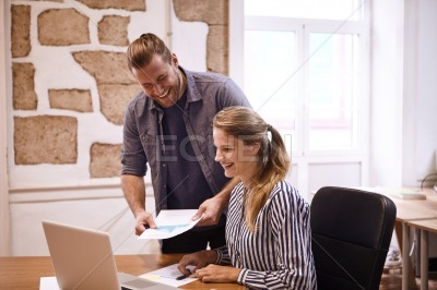Laughing young millenials looking at laptop