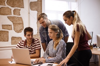 Young business team looking at laptop