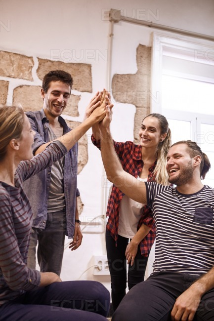 Four happy young people high fiving stock photo