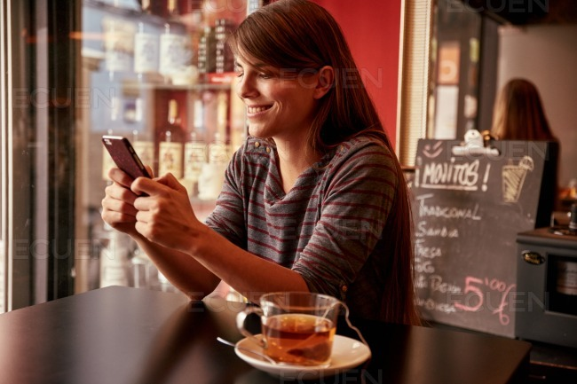 Smiling young lady sitting in a pub stock photo