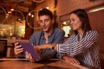 Laughing young couple pointing at tablet