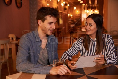 Expectant millenial couple sitting in restaurant