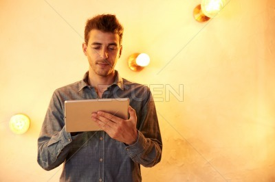 Goodlooking young male texting in tablet