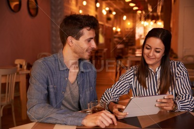 Intimately smiling millenial couple in restaurant