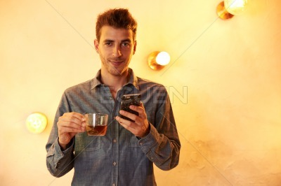 Millennial posing with tea and cellphone