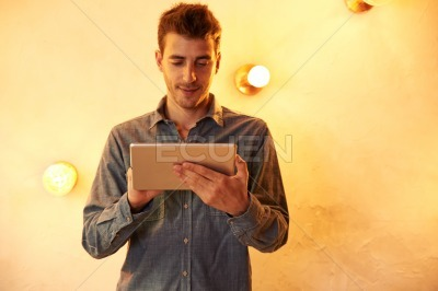 Nice young man texting on tablet