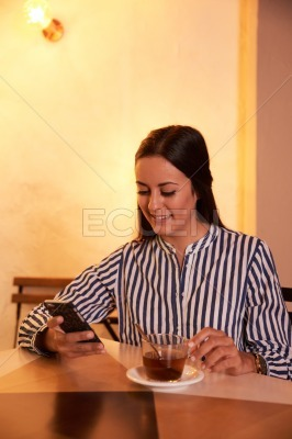 Stunning young lady texting in restaurant