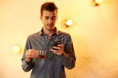Young guy with cellphone and tea
