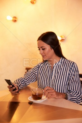 Young millenial texting in a restaurant
