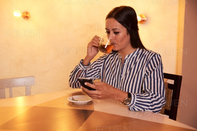 Sipping tea while reading a text message