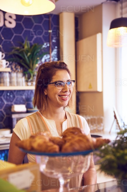 Smiling lady behind plate of croissants stock photo