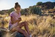Girl sitting on rock looking at cell