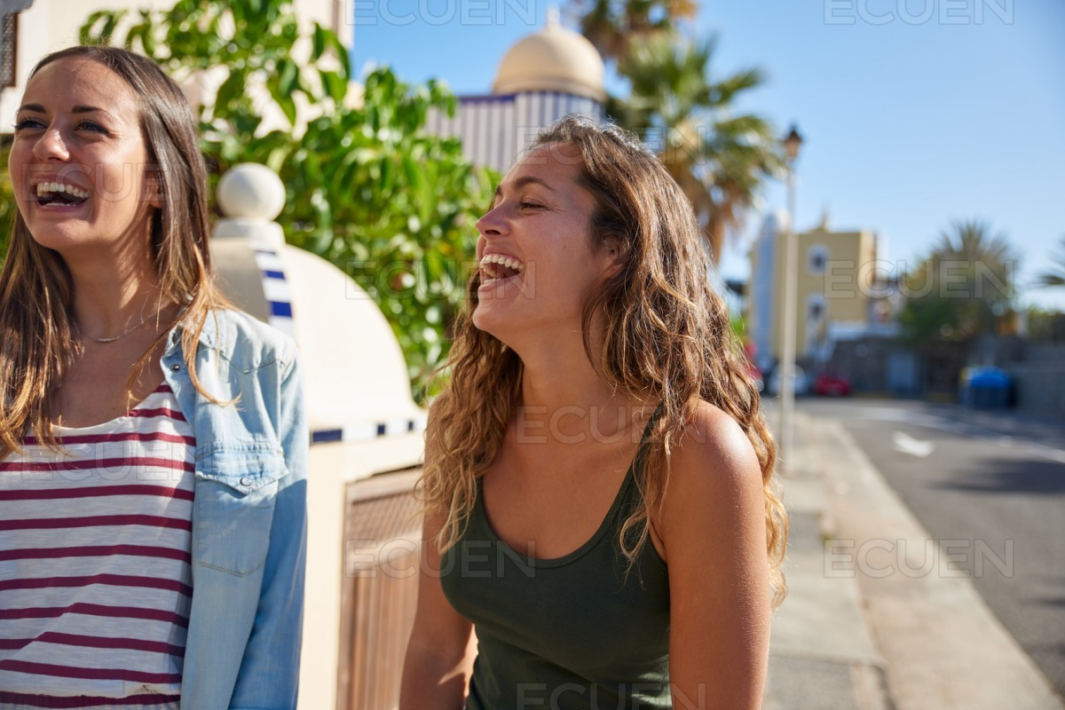 Two beautiful young girls laughing uncontrollably stock photo