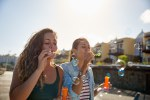 Two beautiful girls blowing some bubbles