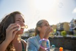 Two charming young ladies blowing bubbles