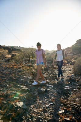 Cute girls walking down rocky path