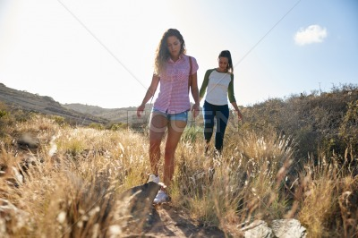 Fit young girls hiking on hill