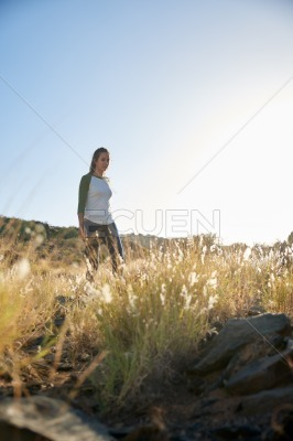 Girl standing on hill in sunlight