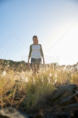 Girl walking on hill in sunshine