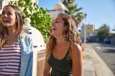 Two beautiful young girls laughing uncontrollably