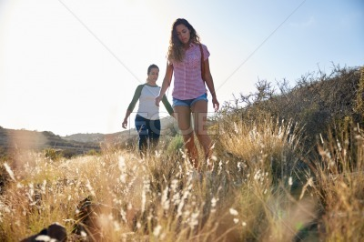 Two concentrating girls hiking on hill