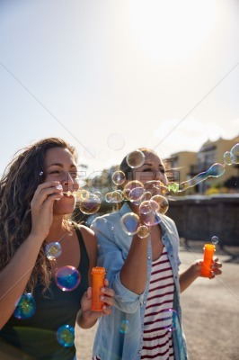 Two girls blowing strings of bubbles