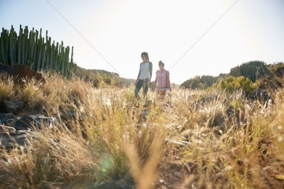Two girls walking a grassy hillside