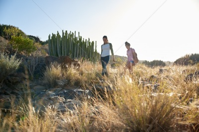 Two girls walking a rocky hillside