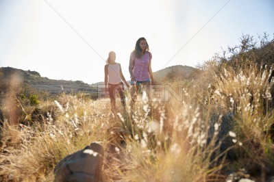 Two healthy girls hiking on hillside