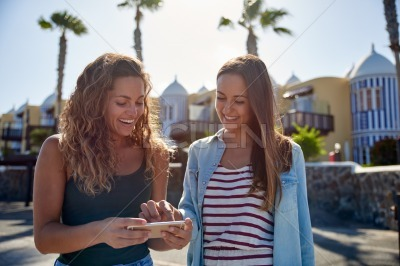 Two laughing girls looking at cellphone