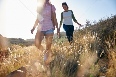 Two strong girls walking on hillside