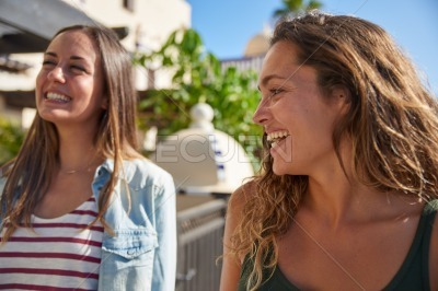 Two young girls laughing and joking