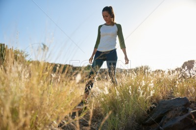 Young girl walking through long grass