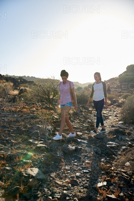 Cute girls walking down rocky path stock photo
