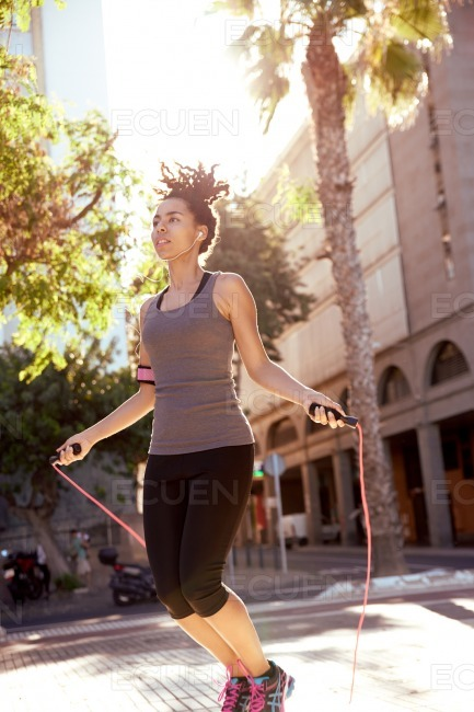 Fit woman skipping with jump rope stock photo