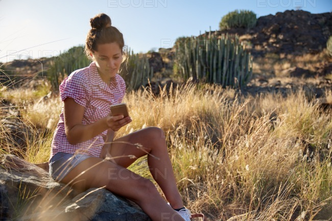 Girl sitting on rock looking at cell stock photo