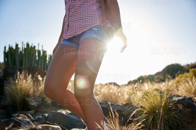 Girl walking downhill holding the sun stock photo