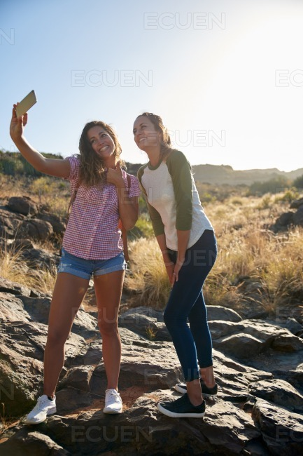 Girls on a rock taking selfies stock photo