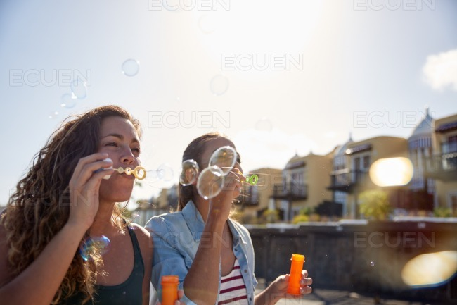 Two happy young girls blowing bubbles