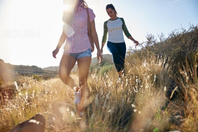 Two strong girls walking on hillside stock photo
