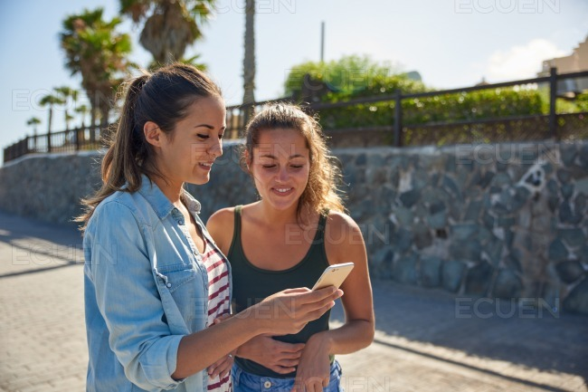 Two young girls looking at cellphone stock photo