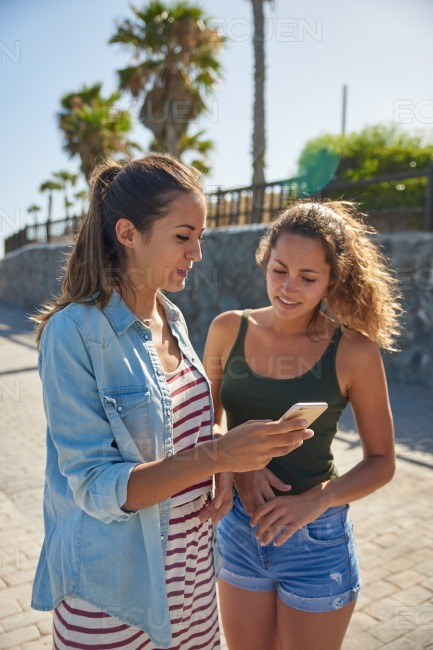 Two young ladies looking at cellphone stock photo
