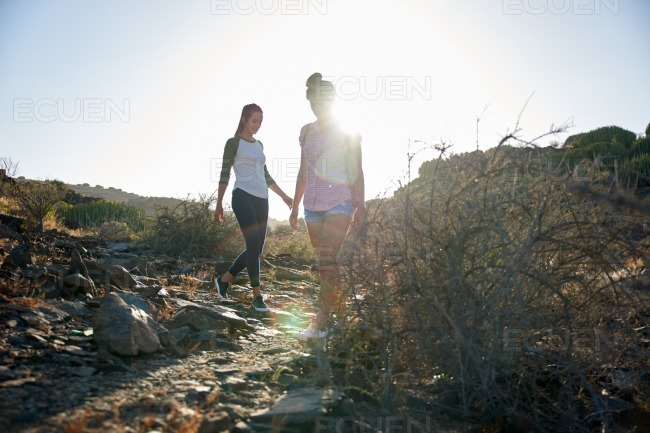 Young girls walking down rocky path stock photo