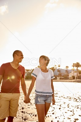 Couple holding hands walking the beach
