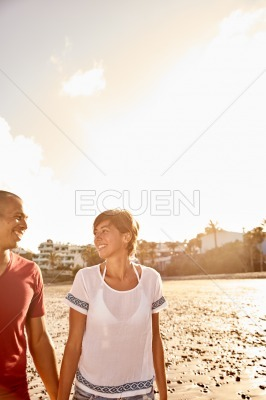 Couple strolling beach while holding hands