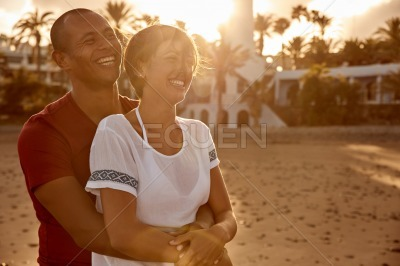 Embracing adult couple laughing with love