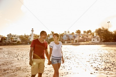 Happy adult couple walking on beach